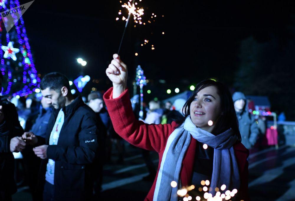 新年慶祝期間,和五彩煙火在一起的女孩——2019年,雅爾塔
