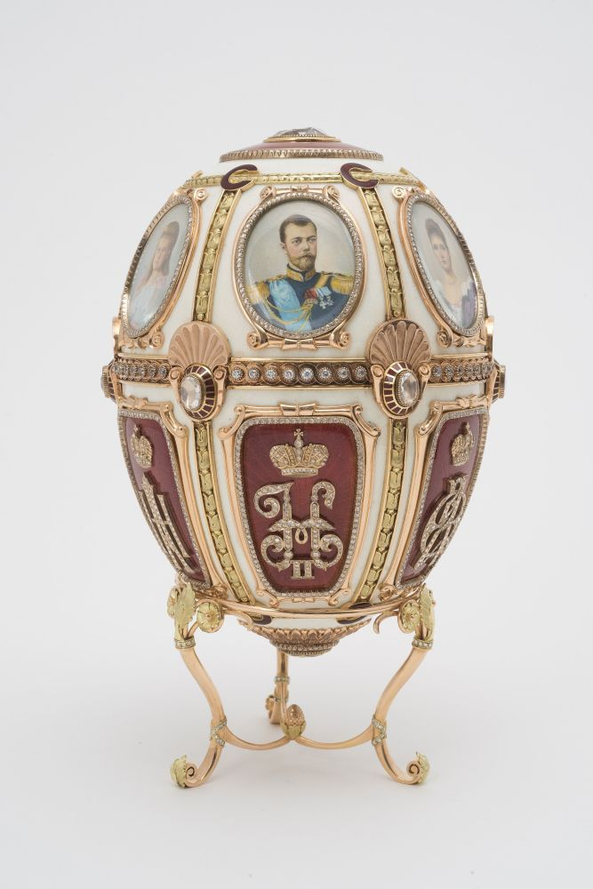 托盘上的复活节彩蛋。彩蛋装饰有沙皇家族名和姓或名和父称的头一个字母交织成图案状的花字和6个带有尼古拉二世、王后及几个女儿肖像的缩面小型物件。
