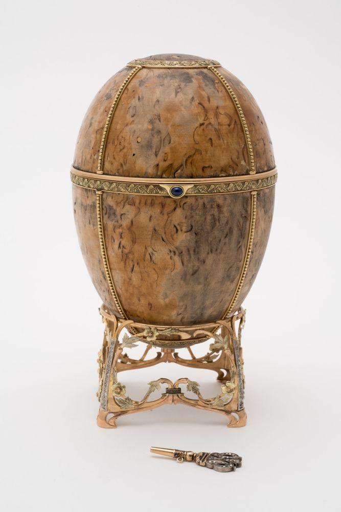 放在沙皇徽章装饰的原装盒子中的带有托盘和扭转钥匙的复活节彩蛋。