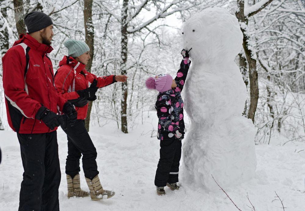 带着孩子的一家人在克里米亚安加尔斯克山口度假期间堆雪人