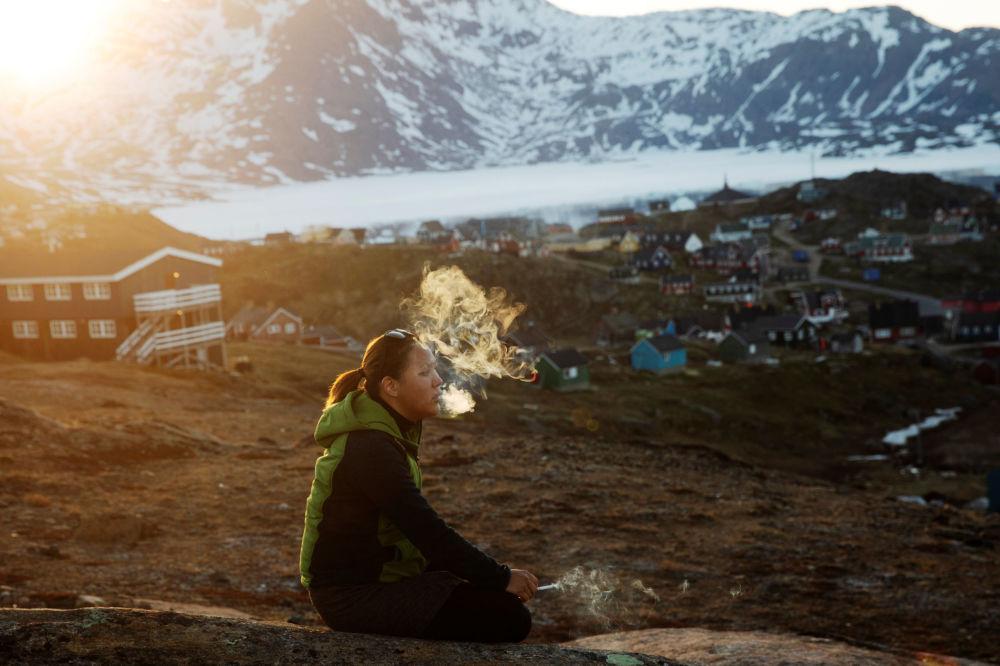 年輕的女孩坐在石頭上,在落日的余暉中抽煙,塔西拉克鎮(Tasiilaq Town),格陵蘭島