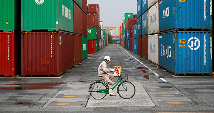 A worker rides a bicycle in a container area at a port
