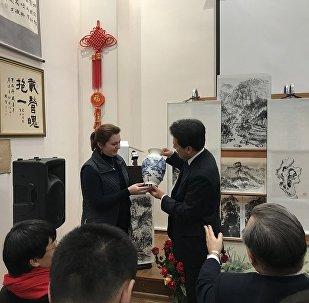 由俄罗斯女画家安娜?多琴科把自己绘制的瓷器赠给出席展览会的中国驻俄罗斯大使