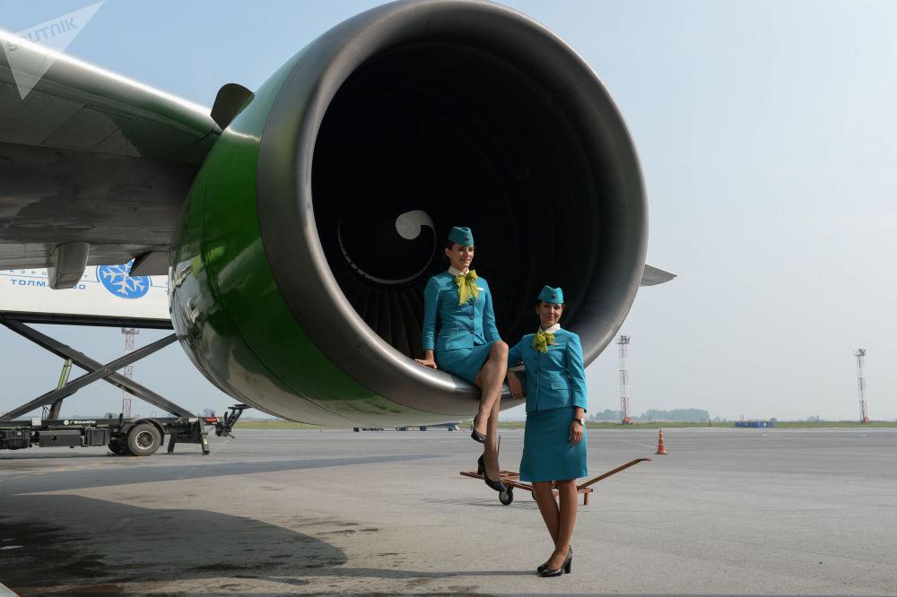 S7航空公司的空姐在新西伯利亚托尔马切沃机场的飞行场地上拍照
