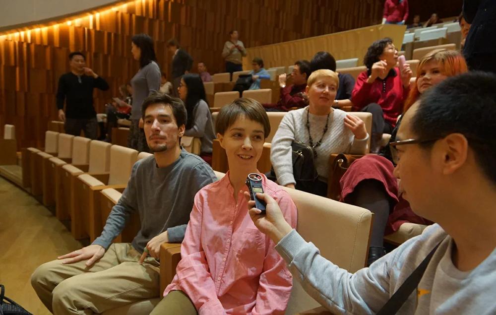 莫斯科市民阿廖娜和阿夫杰伊看了中国乐团的演出感到很兴奋