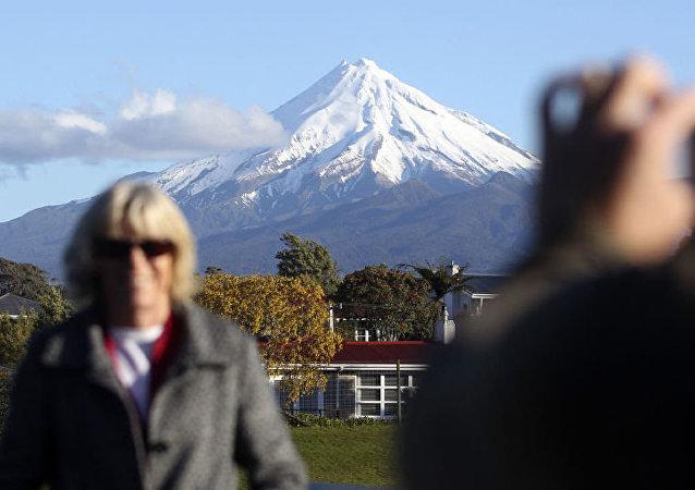 Туристка фотографируется на фоне Вулкана Таранаки. Новая Зеландия
