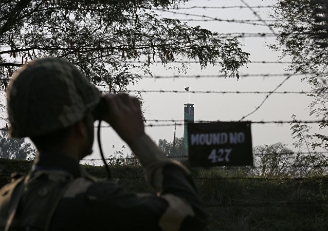 An India's Border Security Force soldier keeps vigil during patrol along the fenced border with Pakistan in Ranbir Singh Pura sector