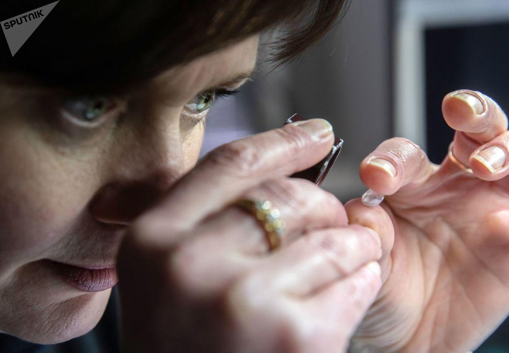 在莫斯科埃罗莎钻石有限责任公司技术和评估车间,一名女员工在鉴定钻石