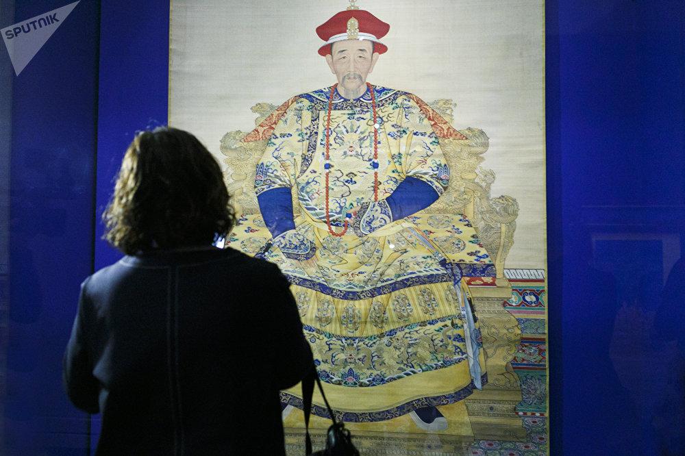 一名女参观者在看乾隆皇帝的肖像