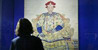 Посетительница выставки смотрит на портрет императора Цяньлуна в парадном одеянии. Эпоха Цин, правление Цяньлун (1736-1796)