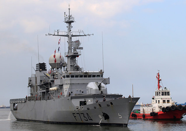 A tugboat escorts French Navy frigate Vendemiaire on arrival for a goodwill visit at a port in Metro Manila