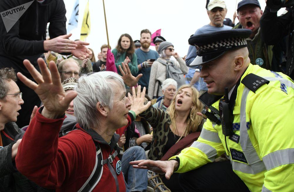 警员在伦敦街头与反环境污染抗议活动参与者交流。