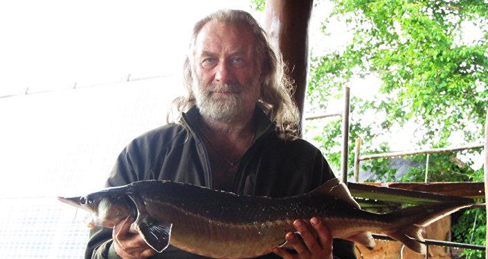 谢尔盖·帕夫洛夫斯基展示猎场旁湖泊中钓出的鲟鱼