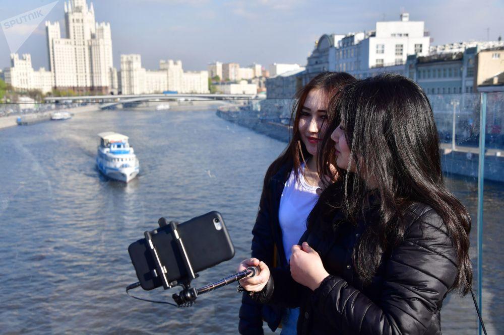 在莫斯科扎里亚季耶回旋镖形浮桥上拍照的女孩。远处是科杰里尼切斯卡娅沿河街上的高楼。