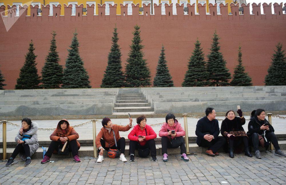 在红场上克里姆林宫墙边拍照的游客们。