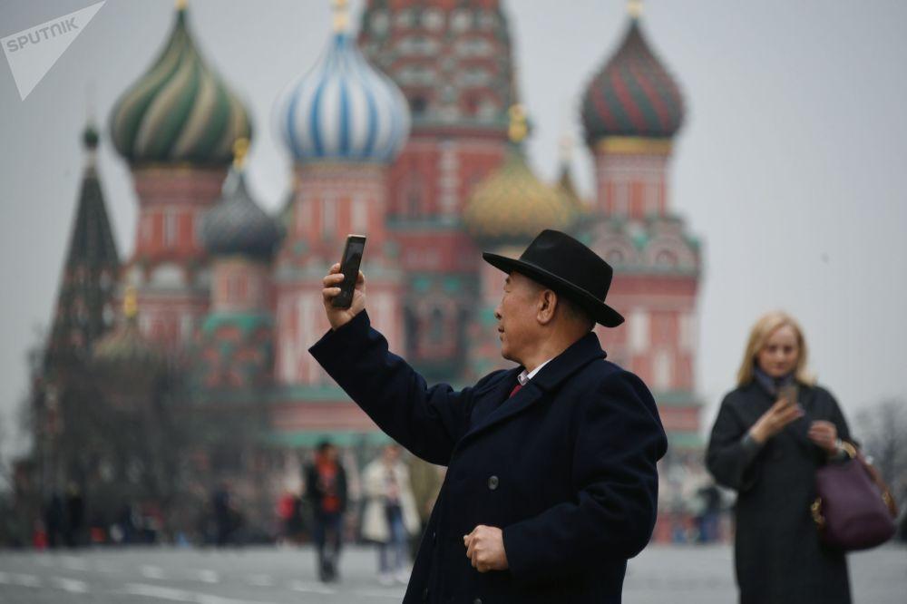 在莫斯科红场上以圣瓦西里教堂为背景拍照的游客。