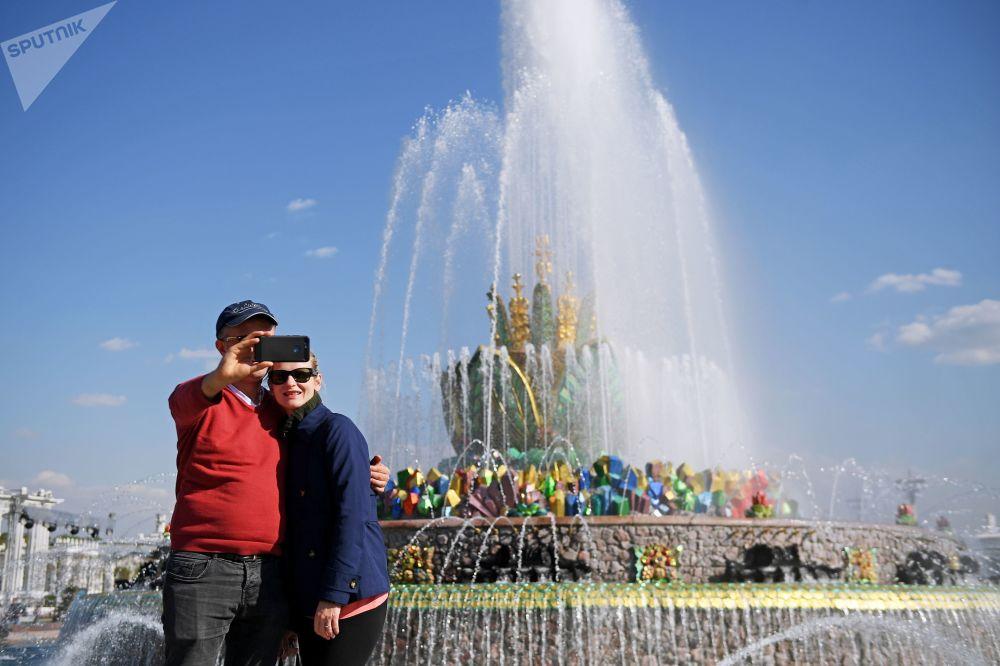 """在莫斯科全俄展览中心已开始工作的""""石花""""喷泉旁拍照的休闲者。"""