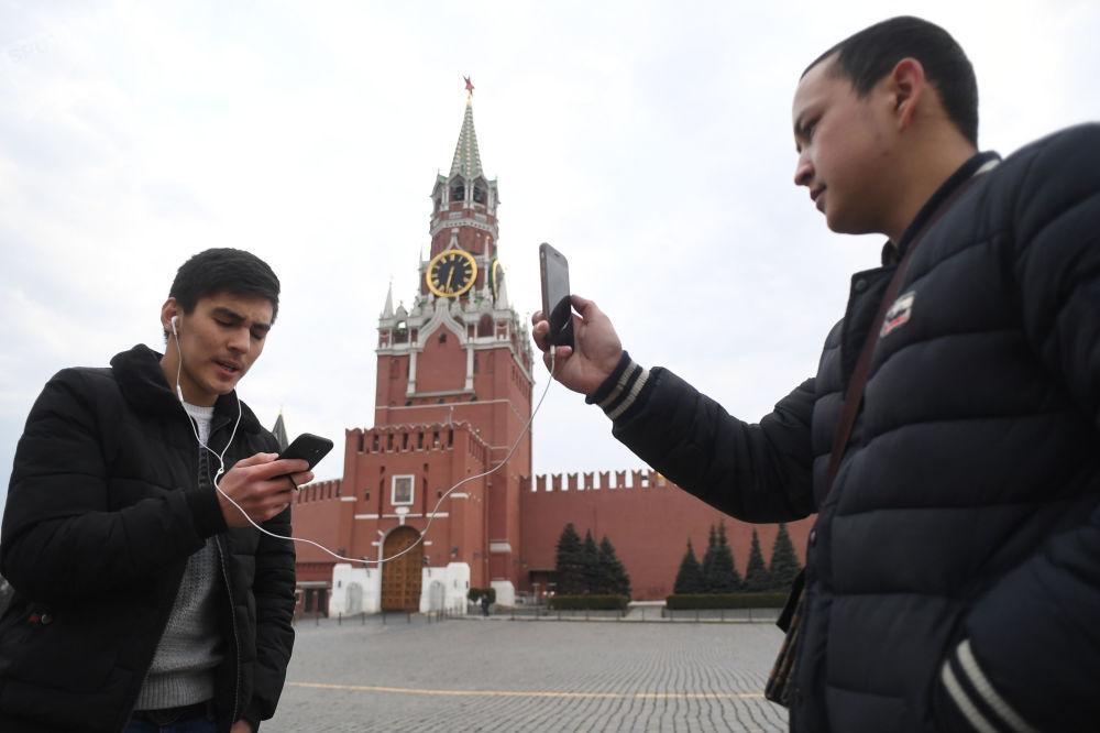 在红场克林姆林宫旁拍照的年轻人。