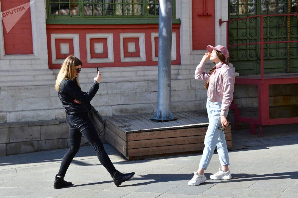 在莫斯科尼科尔斯卡亚街上拍照的女孩们。