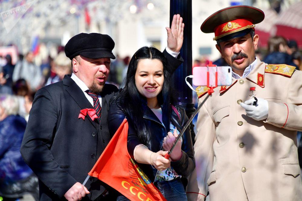 在莫斯科尼科尔斯卡亚街上同身穿列宁服装和斯大林服装的男子合照的女孩。