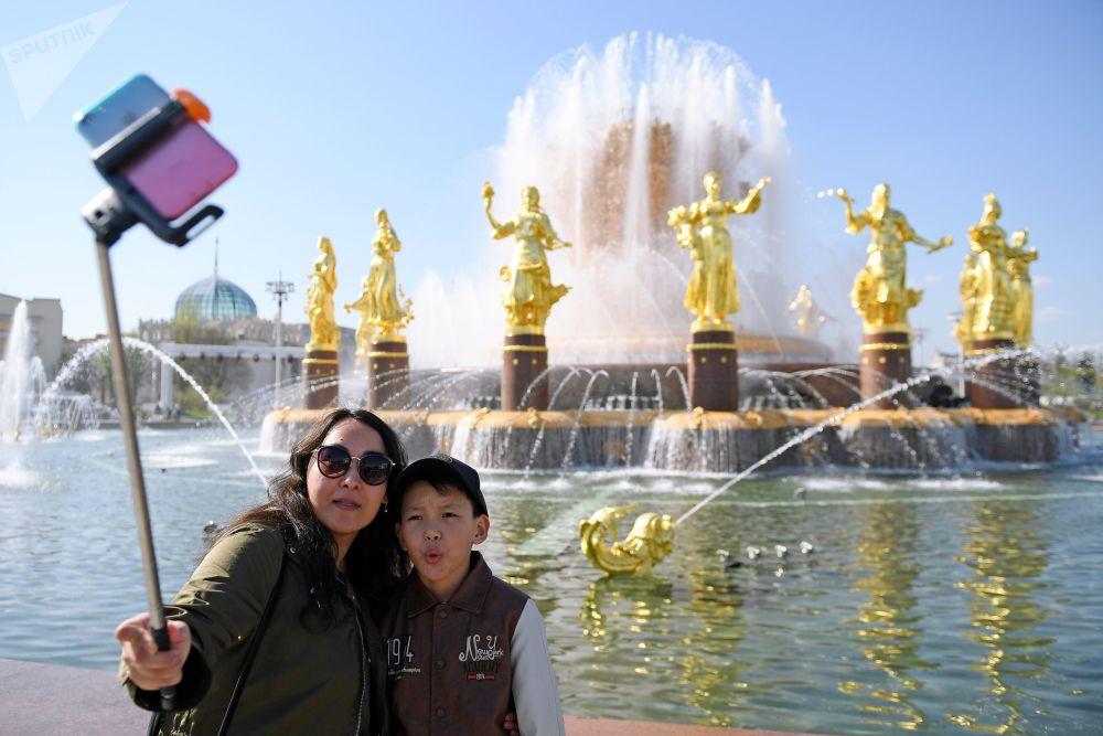 """在全俄展览中心已开始工作的""""人民友谊""""喷泉旁拍照的休闲者。"""