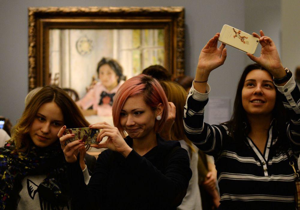 在位于莫斯科克里米亚土堤的特列季亚科夫画廊中瓦列京•谢洛夫的《少女与桃子》画作旁拍照的参观者。