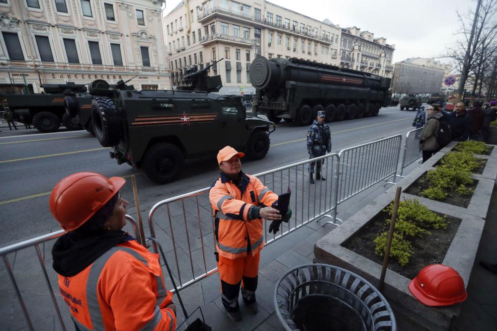 莫斯科胜利日阅兵彩排期间在军事设备队列前自拍的城市工作者。