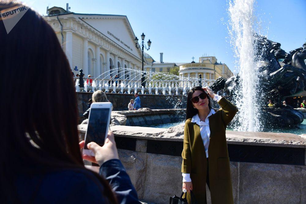 """在莫斯科马涅什广场""""四季""""喷泉旁拍照的女孩。"""