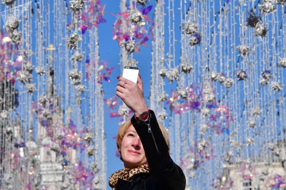 在莫斯科尼科尔斯卡亚街拍照的女子。