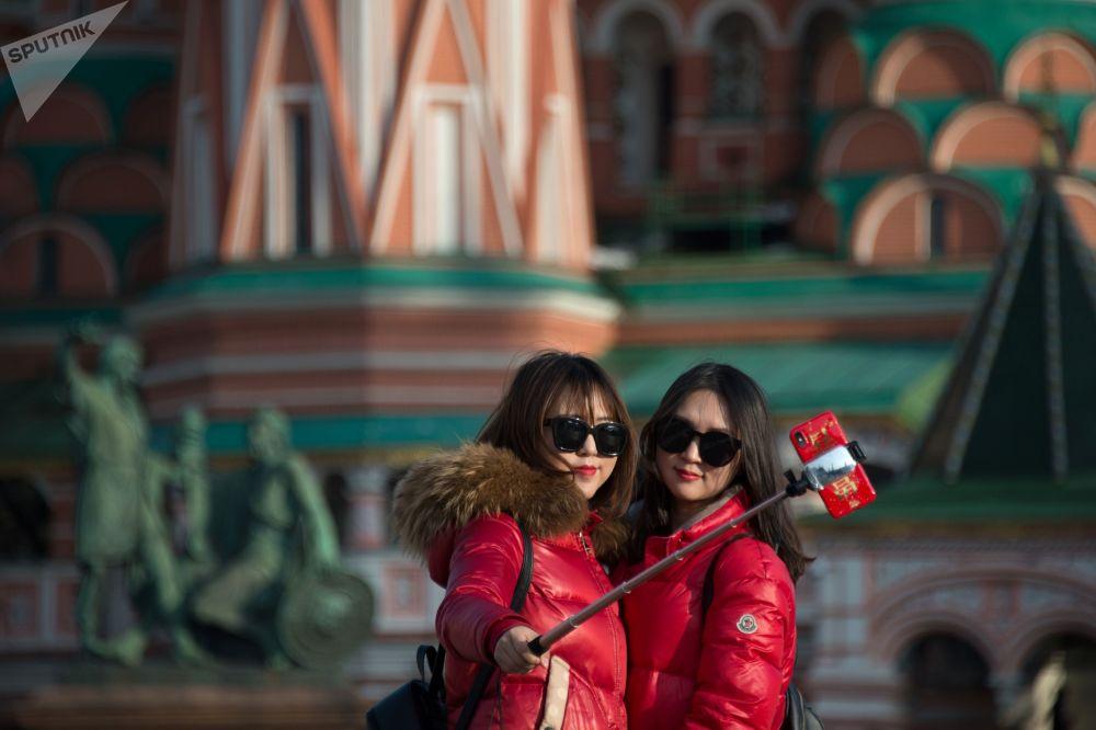 以莫斯科圣瓦西里教堂为背景自拍的女孩们。
