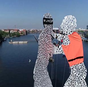 德國積極分子給柏林雕像穿上移民救生衣