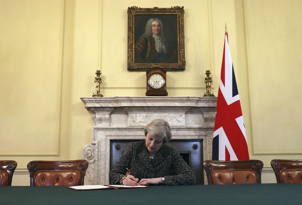 英国首相特蕾莎·梅在致欧盟的脱欧信函上签字。