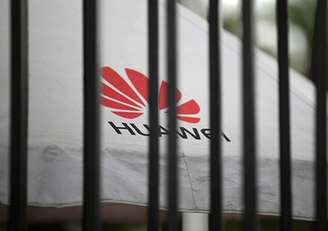 A Huawei logo is seen outside the fence at its headquarters in Shenzhen