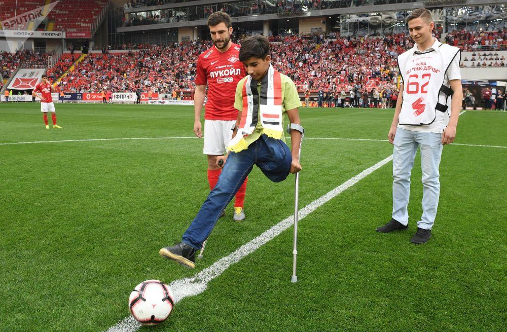 在摄影记者安德烈∙斯捷宁国际摄影赛上赢得金奖的照片《渴望生活》的主角-伊拉克小男孩卡西姆∙阿尔卡吉姆在俄罗斯足球联赛第28轮比赛—莫斯科斯巴达克队和乌法乌法队开始前象征性地踢了一脚球。