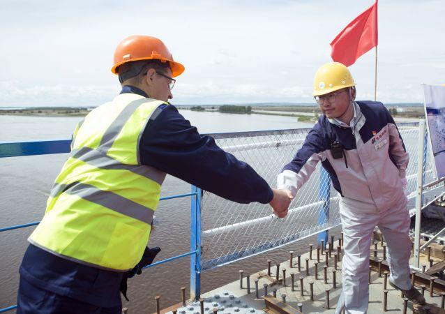 中俄黑河-布拉戈维申斯克跨境公路大桥合龙仪式上具有象征意义的握手。