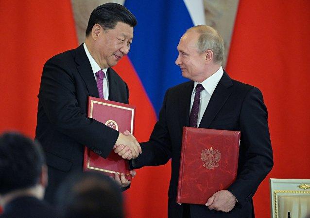 Президент РФ Владимир Путин и председатель Китайской Народной Республики Си Цзиньпин (слева) на церемонии подписания совместных документов по итогам российско-китайских переговоров в Кремле.