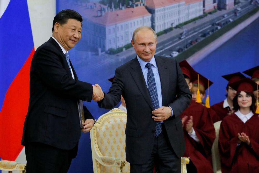 中华人民共和国主席习近平与俄罗斯总统弗拉基米尔·普京在圣彼得堡国立大学授予中国主席习近平名誉博士的庆典上握手致意