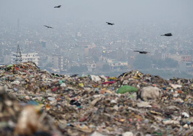 This picture taken on November 13, 2018, shows an Indian trash collector sitting on garbage at the Ghazipur landfill site in New Delhi.
