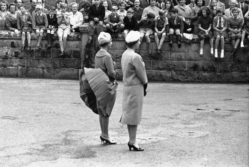 英國女王伊麗莎白二世和瑪格麗特公主在蘇格蘭巴爾莫勒爾城堡等待美國總統艾森豪威爾時,瑪格麗特公主的裙擺被風吹起。