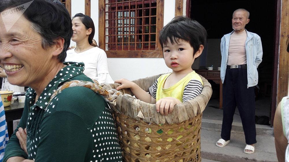 小公主舒服地坐在奶奶身后的篮子里。