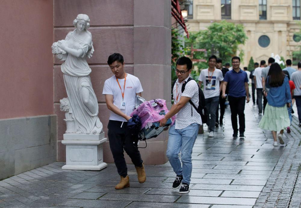 """华为公司员工拿着设备路过雕像,中国东莞。为公司研发人员而设的""""牛角""""园区按欧洲风格建造"""