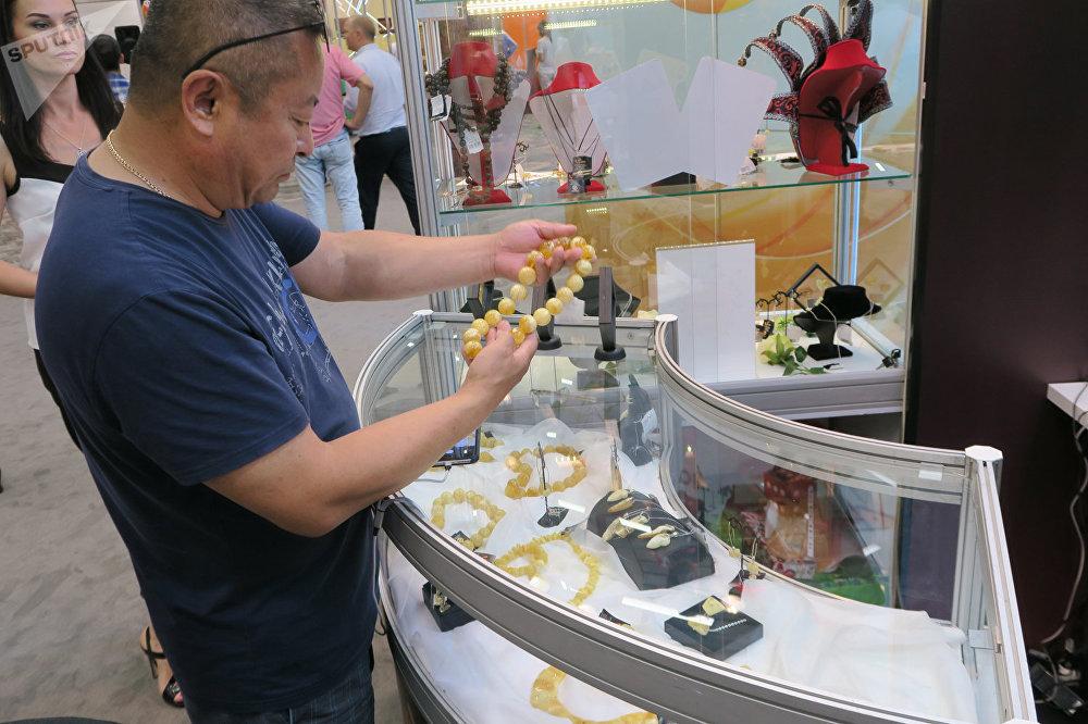 参观展会的中国人在选择白蜜蜡珠子做成的项链。其价格超过了3万元。