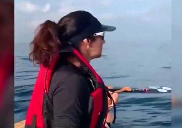 巨型鲸鱼在受惊的女划艇手面前做空中翻转动作