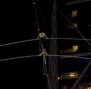 特技表演家在紐約時代廣場摩天大樓之間走鋼絲