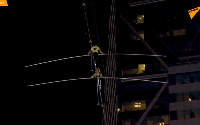 特技表演家在纽约时代广场摩天大楼之间走钢丝