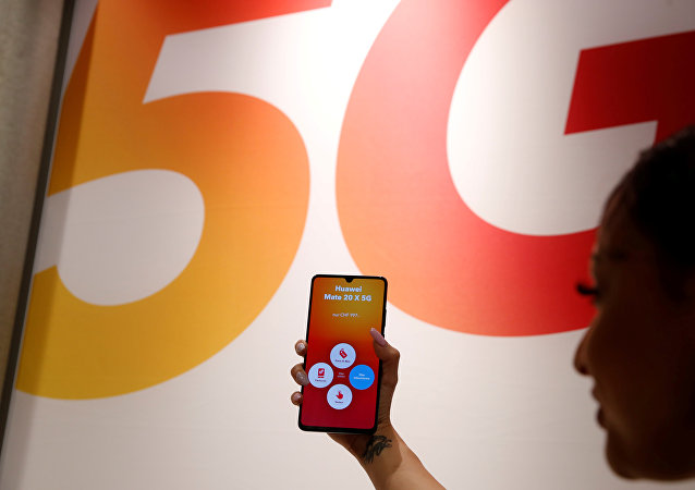 n employee displays a Huawei 5G Smartphone Mate 20X smartphone at a Sunrise telecommunications shop in Opfikon
