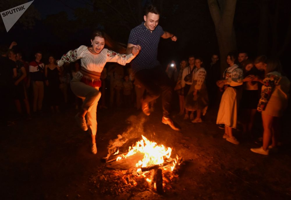 烏克蘭小伙和姑娘在伊凡·庫帕拉節上跳過篝火