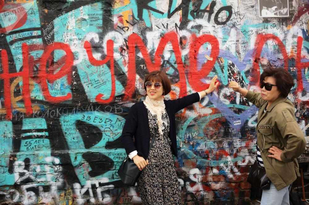 游客在莫斯科老阿尔巴特维克多·崔纪念墙旁