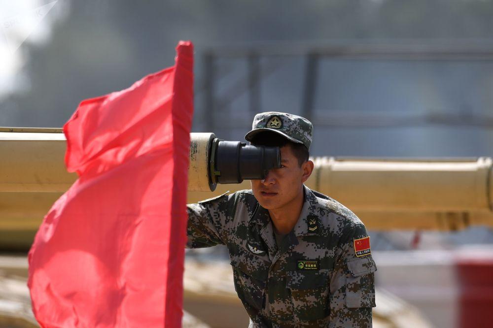 """一名中国军人在""""坦克两项-2019""""国际比赛前瞄靶射击。"""