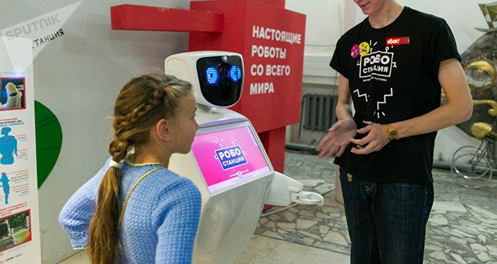 机器人站的工作人员马克西姆为年轻的客人介绍人形机器人的各种能力